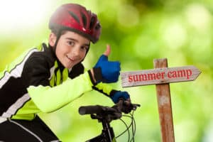 boy on bike excited about summer camp